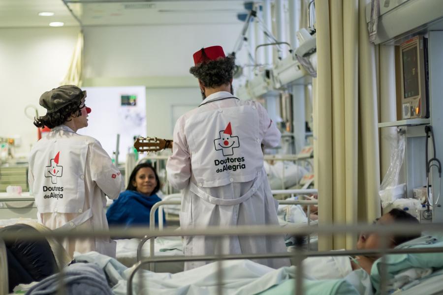 dois palhaços interagindo com uma criança e sua mãe dentro da UTI de um hospital